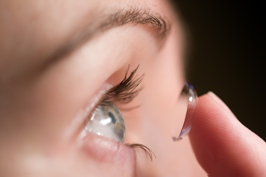 woman putting in contact lens in her eyes